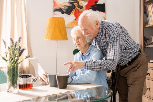 Coppie senior moderne che per mezzo del computer portatile