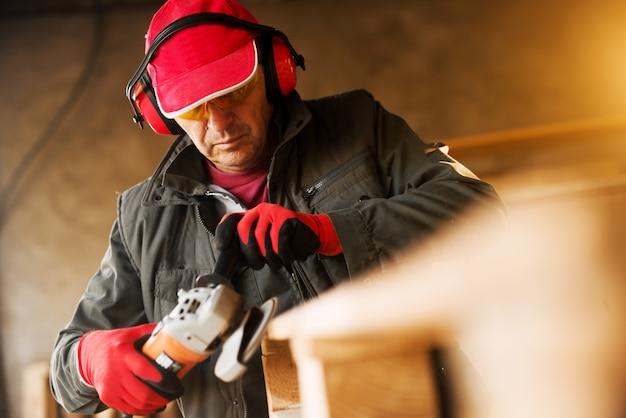 Lavoratore senior moderno del tessuto in uniforme professionale e protezione che lavora con una smerigliatrice elettrica su un pallet di legno.
