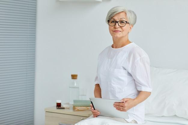 Moderna donna senior seduta sul letto in reparto ospedaliero tenendo la tavoletta digitale