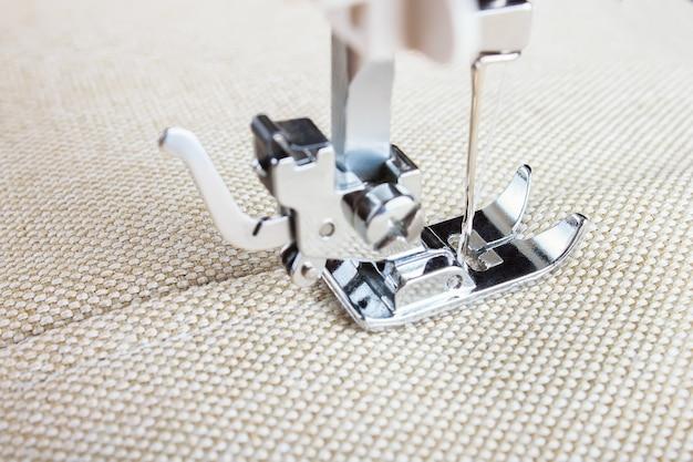 Il piedino per macchina da cucire moderna esegue una cucitura su tessuto beige. processo di cucito