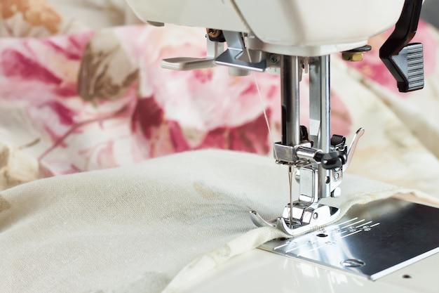 Il moderno piedino per macchina da cucire esegue una cucitura su tessuto colofrul. processo di cucito