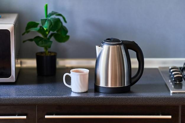 Bollitore in acciaio inossidabile moderno in metallo argentato e tazza di vetro bianca per preparare il tè in cucina a casa