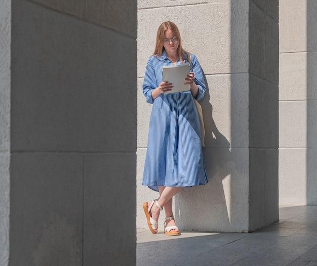 Moderna e intelligente giovane studentessa intelligente in piedi vicino all'edificio universitario e leggendo libri e programmi di studio