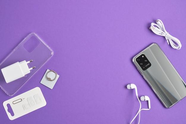 Smartphone moderno e accessori su sfondo viola, vista dall'alto, spazio copia, set per smartphone, custodia, vetro protettivo, cuffie, caricatore fotocamera hd 100x