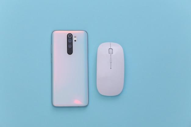 Retro dello smartphone moderno con lenti e mouse per pc bianco su sfondo blu
