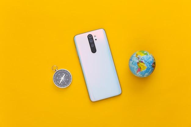 Smartphone e globo moderni, bussola su giallo. concetto di viaggio