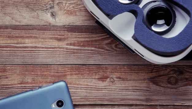 Smartphone moderno con schermo vuoto e occhiali per realtà virtuale su fondo in legno.