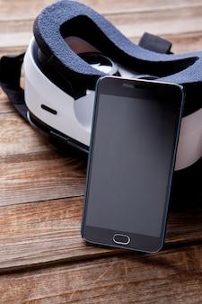 Smartphone moderno con schermo vuoto e occhiali per realtà virtuale sul tavolo di legno.