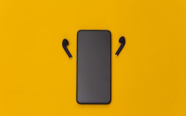 Smartphone moderno con auricolari wireless su sfondo giallo.