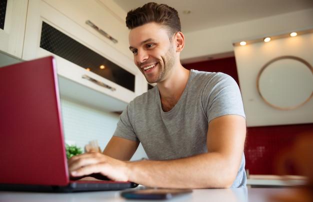 L'uomo sicuro e sorridente moderno lavora al computer portatile sulla cucina domestica