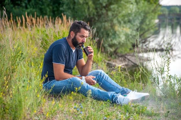 Fumatore moderno che soffia molto fumo usando la sigaretta elettronica vape.