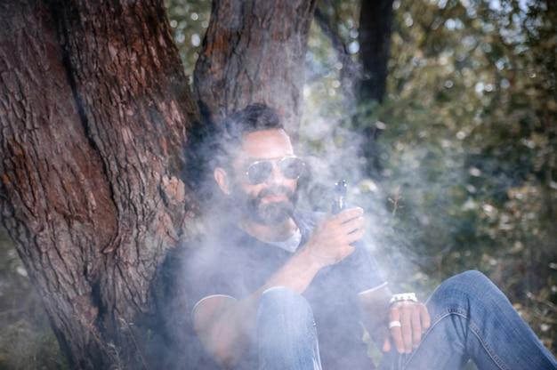 Fumatore moderno che gode di una sigaretta elettronica all'aria aperta