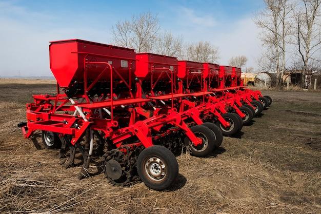 Macchina moderna per la semina. semina del trattore agricolo. aratro rosso combinato. semina nei campi agricoli in primavera.