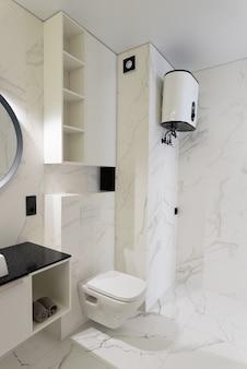 Bagno moderno e spazioso con piastrelle in marmo con vasca da bagno bianca e lavandino vista laterale