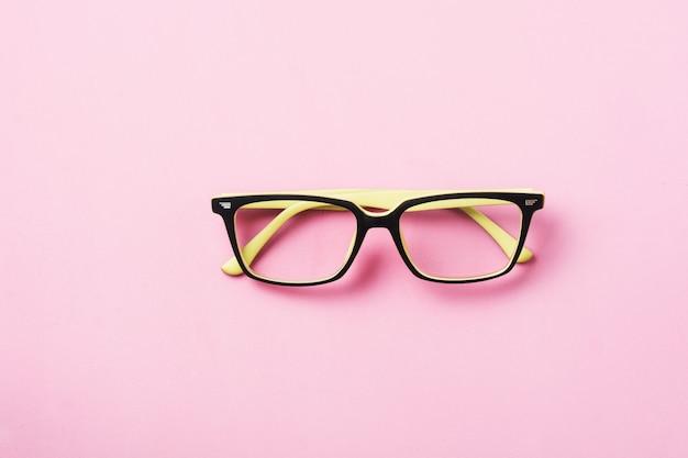 Occhiali da vista moderni o occhiali da vista isolati su sfondo rosa. vista dall'alto. bandiera. modello.