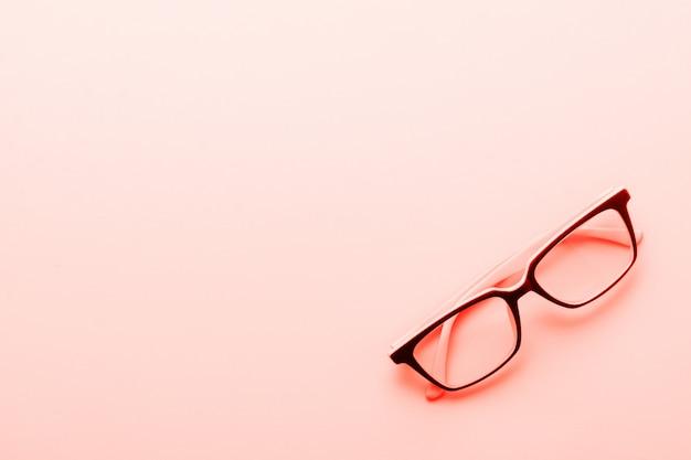 Occhiali moderni occhiali isolato su sfondo giallo. colore di corallo vivente alla moda dell'anno 2019. vista dall'alto.