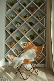 Interni moderni primaverili con una libreria incorporata e una sedia in pelle.soggiorno lussuoso e design degli interni .luce del giorno