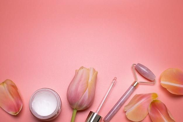 Layout moderno per la cura della pelle primaverile vista dall'alto piatto rullo viso e petali al quarzo rosa