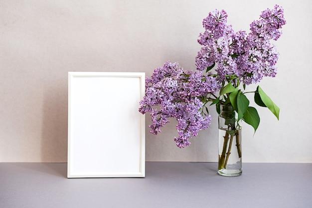 Moderna scena di natura morta di mock up cornice per foto e bouquet di lillà