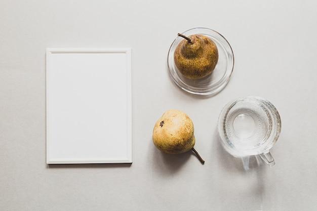 Natura morta moderna con pere vuote bianche della cornice e un bicchiere d'acqua