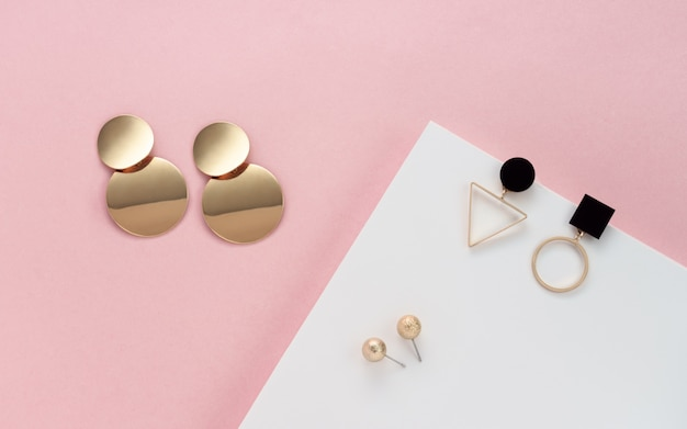 Orecchini a bottone moderni sulla parete di colori bianco e rosa