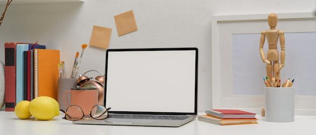 Tavolo da studio moderno con laptop mock-up, bicchieri, strumenti di pittura, forniture e decorazioni