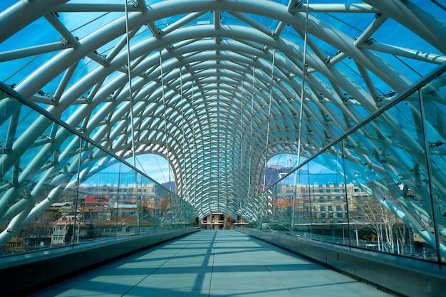 Design moderno ed elegante in vetro e metallo, ponte pedonale sul fiume kura a tbilisi. tbilisi, georgia - 17.03.2021