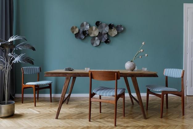 Interiore della sala da pranzo moderna ed elegante con tavolo in legno glamour, sedie eleganti, parquet in legno e decorazioni di design. modello. home decor. concetto minimalista di interior design.