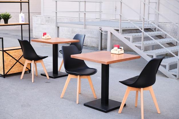 Interni moderni ed eleganti di un caffè o un ristorante di strada. tavoli e sedie da esterno vuoti sulla strada