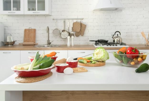 Interiore della cucina moderna ed elegante con frutta e verdura sul tavolo.