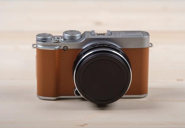 Colore marrone della fotocamera mirrorless moderna ed elegante su una tavola di legno chiaro