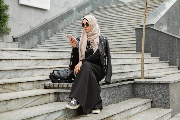 Moderna ed elegante donna musulmana in hijab, giacca di pelle e abaya nera che cammina in una strada cittadina usando lo smartphone