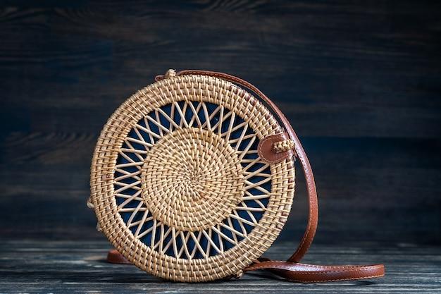 Elegante borsa di paglia rotonda moderna sul legno