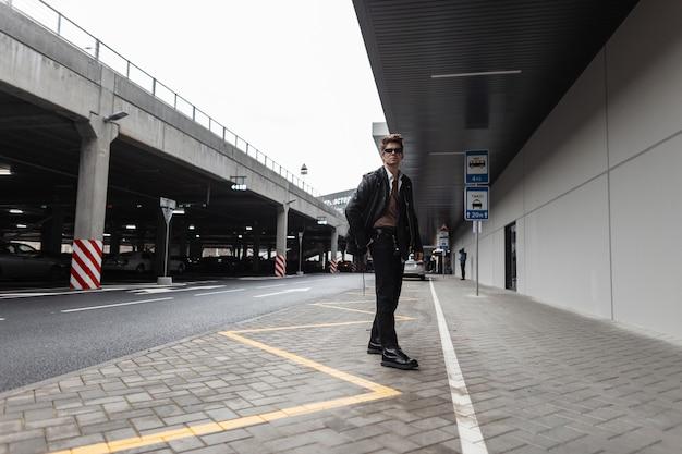 Moderno ed elegante giovane hipster con una giacca di pelle nera in jeans con stivali in occhiali da sole cammina per strada vicino al parcheggio. bel modello alla moda in abiti alla moda in città.