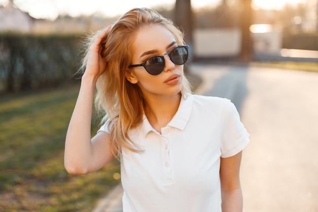 Donna moderna alla moda giovane hipster in t-shirt polo bianca alla moda in occhiali da sole neri stare in piedi e in posa sulla strada. bella ragazza americana.