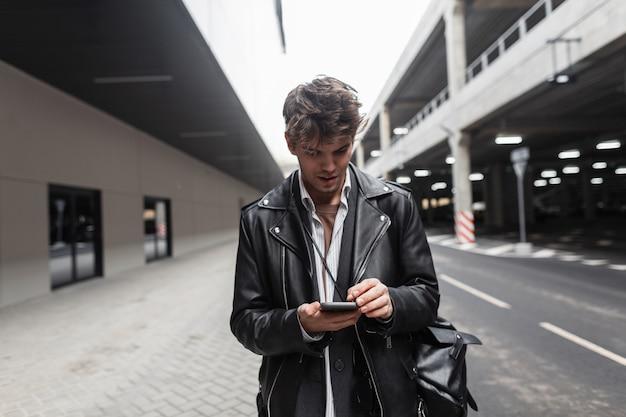 Moderno ed elegante modello di giovane uomo in giacca di pelle nera con zaino con acconciatura tiene il telefono in mano per strada. ragazzo attraente hipster in abiti alla moda si alza e guarda lo smartphone.