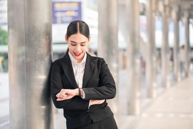 Bella donna felice sorridente riuscita moderna di affari che guarda orologio con lo spazio della copia