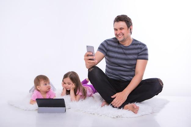 Le moderne tecnologie nella vita di tutti i giorni: un uomo parla al telefono attraverso un auricolare, i bambini guardano un cartone animato su un tablet. hobby e svago con i gadget. genitore con ragazze sul pavimento