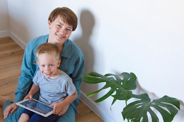 Le moderne tecnologie nella vita di tutti i giorni una donna e un bambino guardano un tablet sul pavimento. hobby e svago con i gadget. vacanze in famiglia, trascorrere del tempo mamma e figlio insieme a casa.