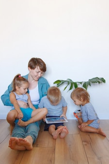 Le moderne tecnologie nella vita di tutti i giorni una donna e un bambino guardano un tablet sul pavimento. hobby e svago con i gadget. vacanze in famiglia, trascorri del tempo mamma e figlio insieme a casa.