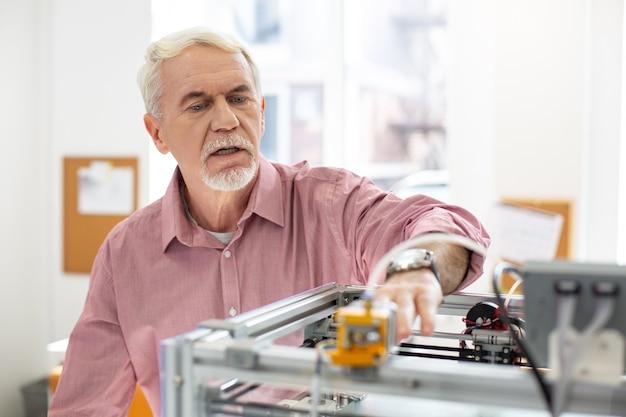Tecnologie moderne. piacevole uomo anziano che gestisce una stampante 3d e stampa qualcosa mentre si lavora in ufficio
