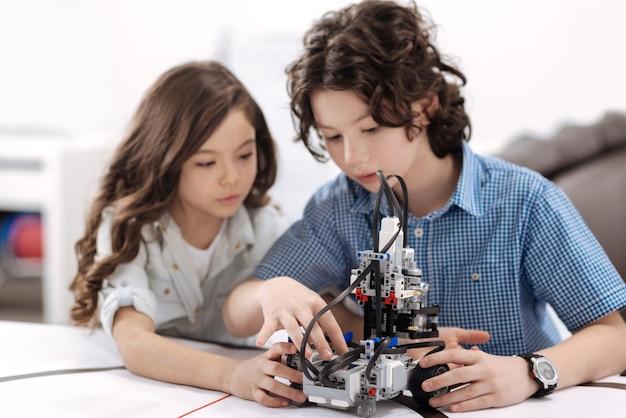 Tecnologie moderne in uso. piacevoli bambini attenti e concentrati seduti a scuola e creano robot mentre esprimono interesse