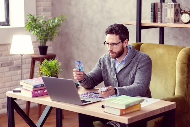 Tecnologia moderna. simpatico cartomante professionista che tiene una carta dei tarocchi davanti allo schermo del laptop durante una sessione online