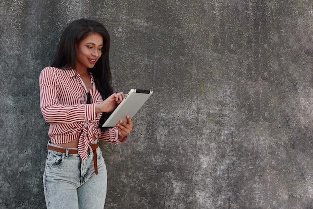 Giovane ragazza castana di tecnologia moderna che sta sulla parete grigia facendo uso dell'applicazione sulla compressa digitale