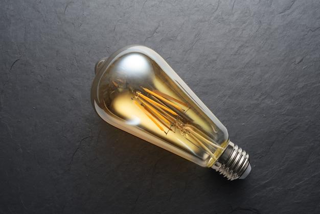 Lampadina a filamento led edison trasparente moderna su sfondo nero ardesia