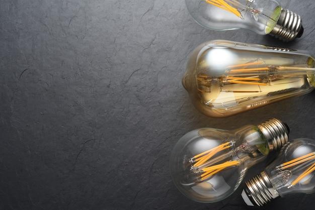 Lampadine moderne trasparenti del filamento del led su fondo nero dell'ardesia. copia spazio