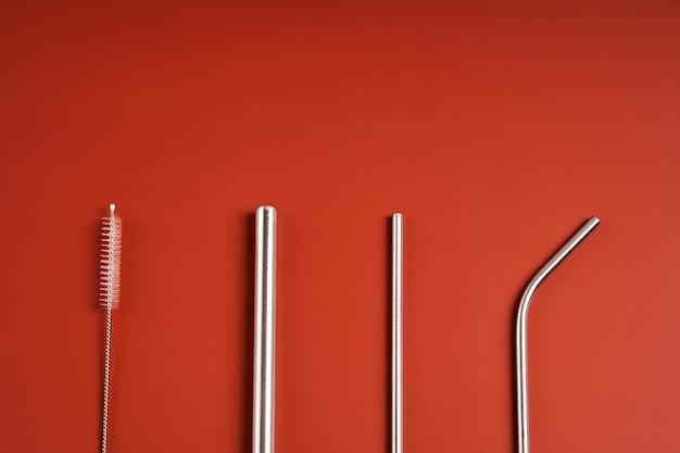 La tendenza moderna attenta all'ambiente. self kit di cannucce per bevande riutilizzabili in metallo scuro di vari diametri e forme con strumento di pulizia.