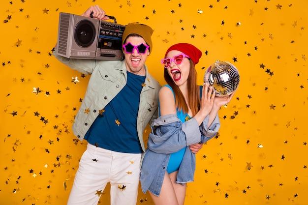 Tendenza moderna due persone studenti godono festa tenere cassetta record boom box discoteca palla coriandoli caduta volare indossare denim jeans giacca costume da bagno camicia pantaloncini isolato brillante brillante colore sfondo