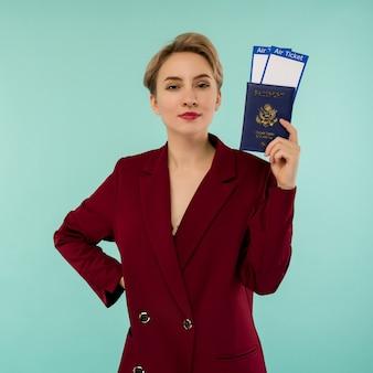 Una donna sorridente alla moda moderna in abito rosso con biglietti aerei e un passaporto in mano.