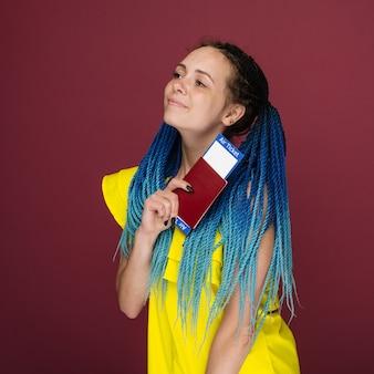 Una donna sorridente alla moda moderna in abito giallo con biglietti aerei e un passaporto in mano. la giovane ragazza vaga osserva da parte. concetto di viaggio